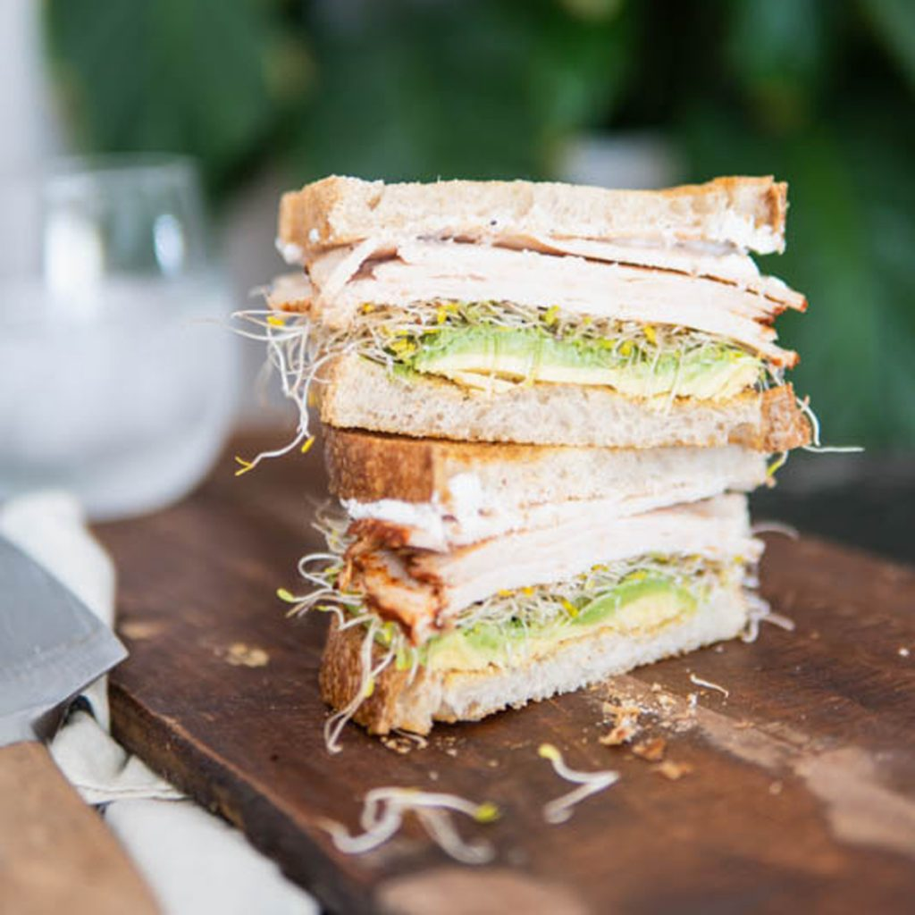 Stacked sourdough sprout chicken sandwich.