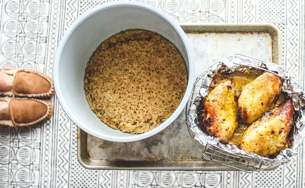 The bowl of the Ninja Foodie pressure cooker with rice pilaf in the bottom and the chicken on a wire rack.