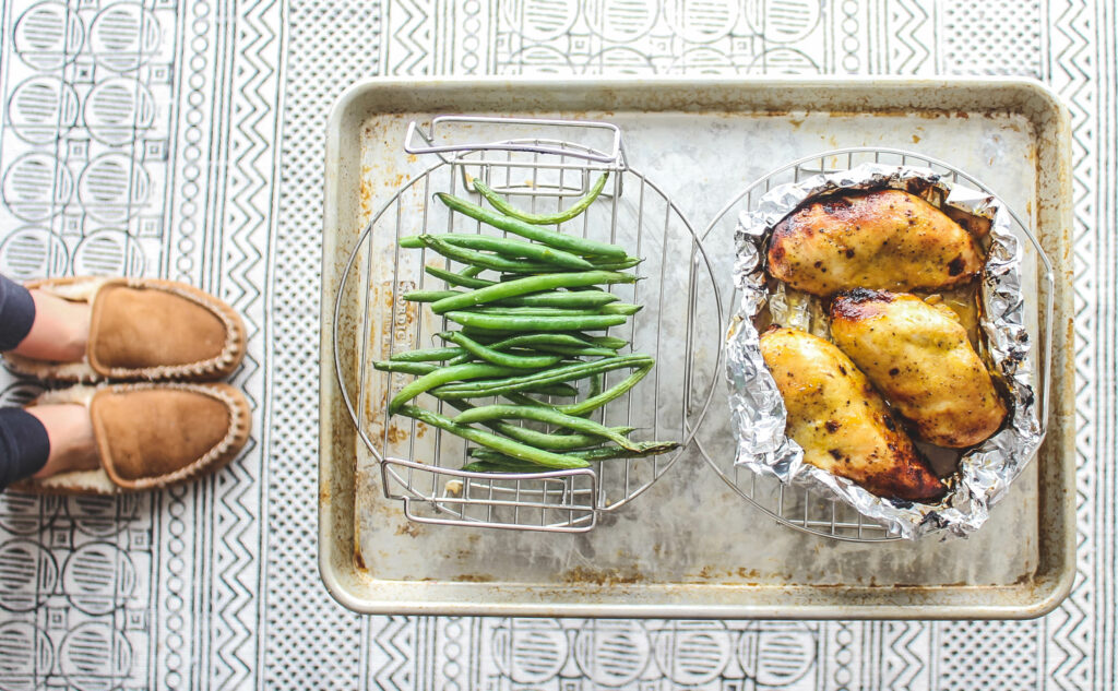 Green beans placed on a wire rack and chicken placed on another, all to be set inside the Ninja Foodie pressure cooker.