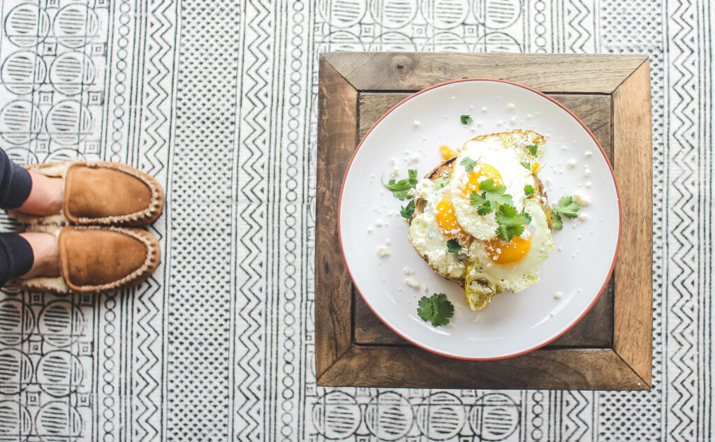 1 stack of New Mexico enchiladas with 3 fried eggs, cotija cheese and cilantro.