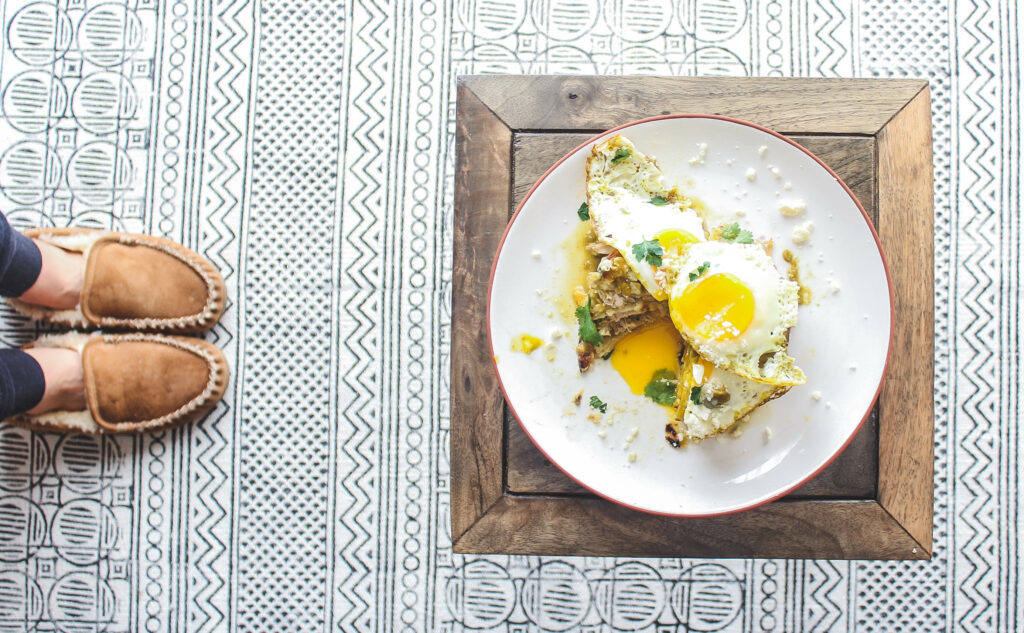 A bite taken out of 1 stack of New Mexico enchiladas with 3 fried eggs, cotija cheese, cilantro.