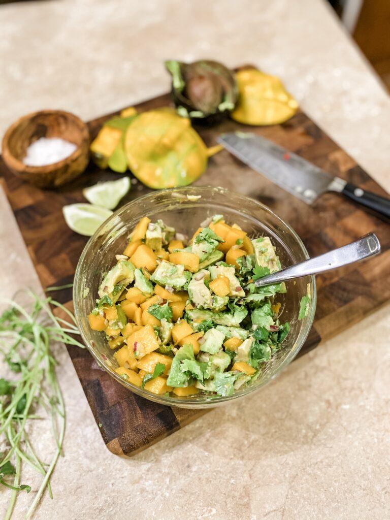 5-Minute Mango Guac in a bowl onto of a cutting board.