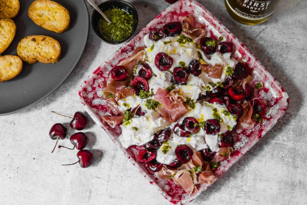 plate of burrata, cherry, prosciutto and chimichurri.