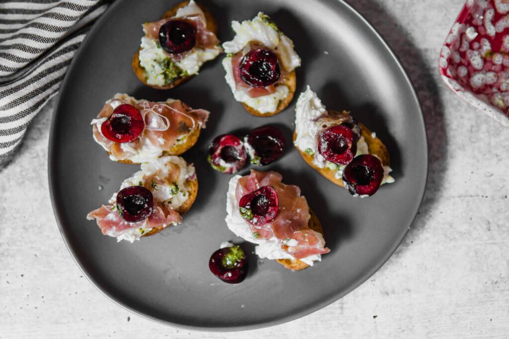 plate of burrata, cherry and prosciutto crostini.