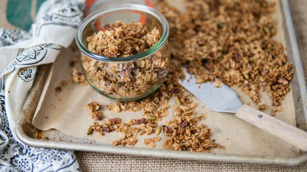 Parchment-line baking sheet with Healthy Homemade Granola and a jar of cooled granola.
