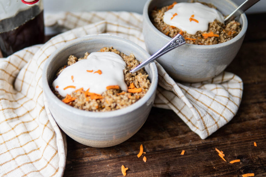 two bowls of carrot cake morning oats with cream cheese yogurt topping.
