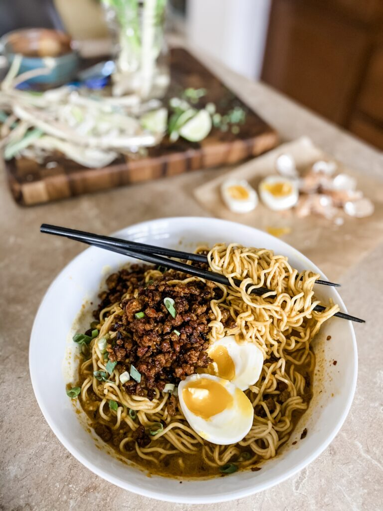 Crispy Lamb ramen Noodles on the counter with soft boiled egg and chopsticks.