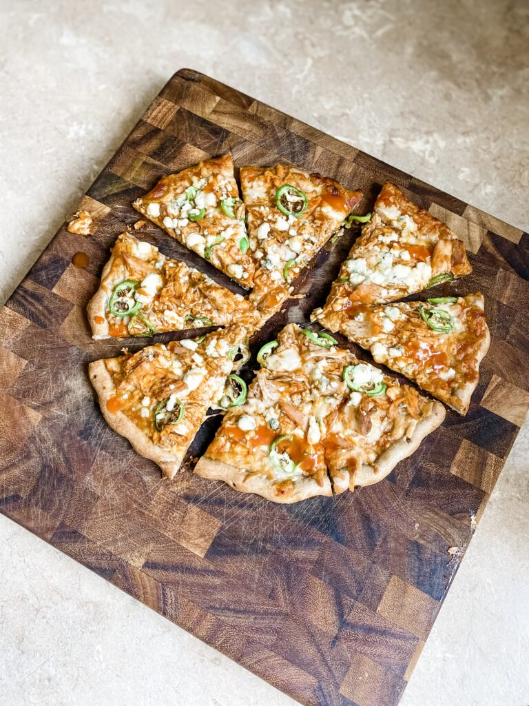 Easy buffalo chicken pizza cooked on a cutting board.
