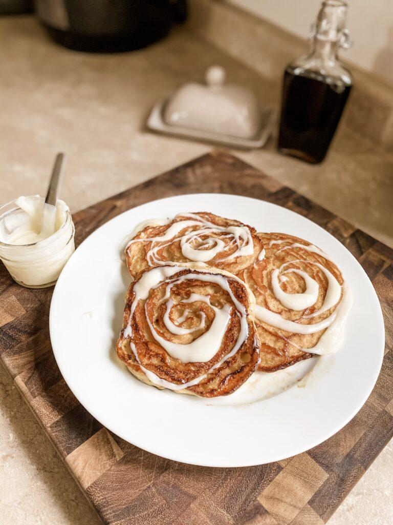 Three cinnamon swirl pancakes with frosting.