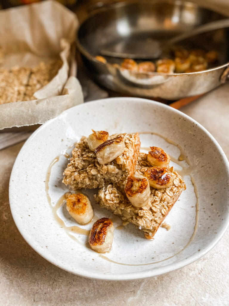 Baked Banana Oatmeal in a finished plate with browned bananas and maple syrup.