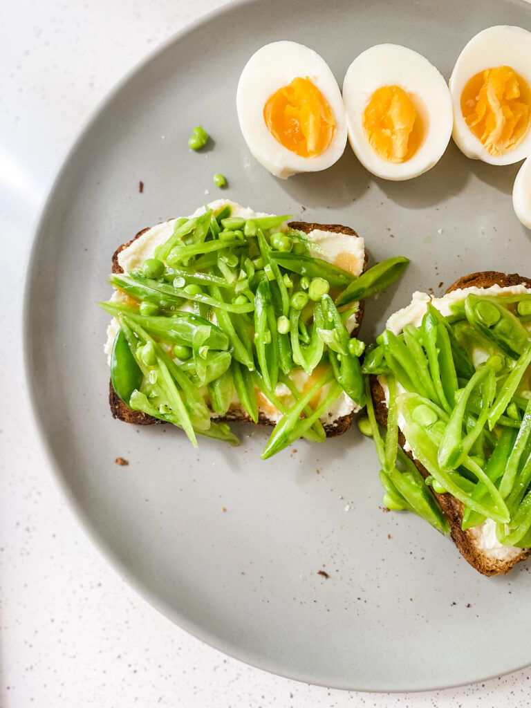 Plate of Whipped Ricotta Pea Toast with soft boiled eggs.