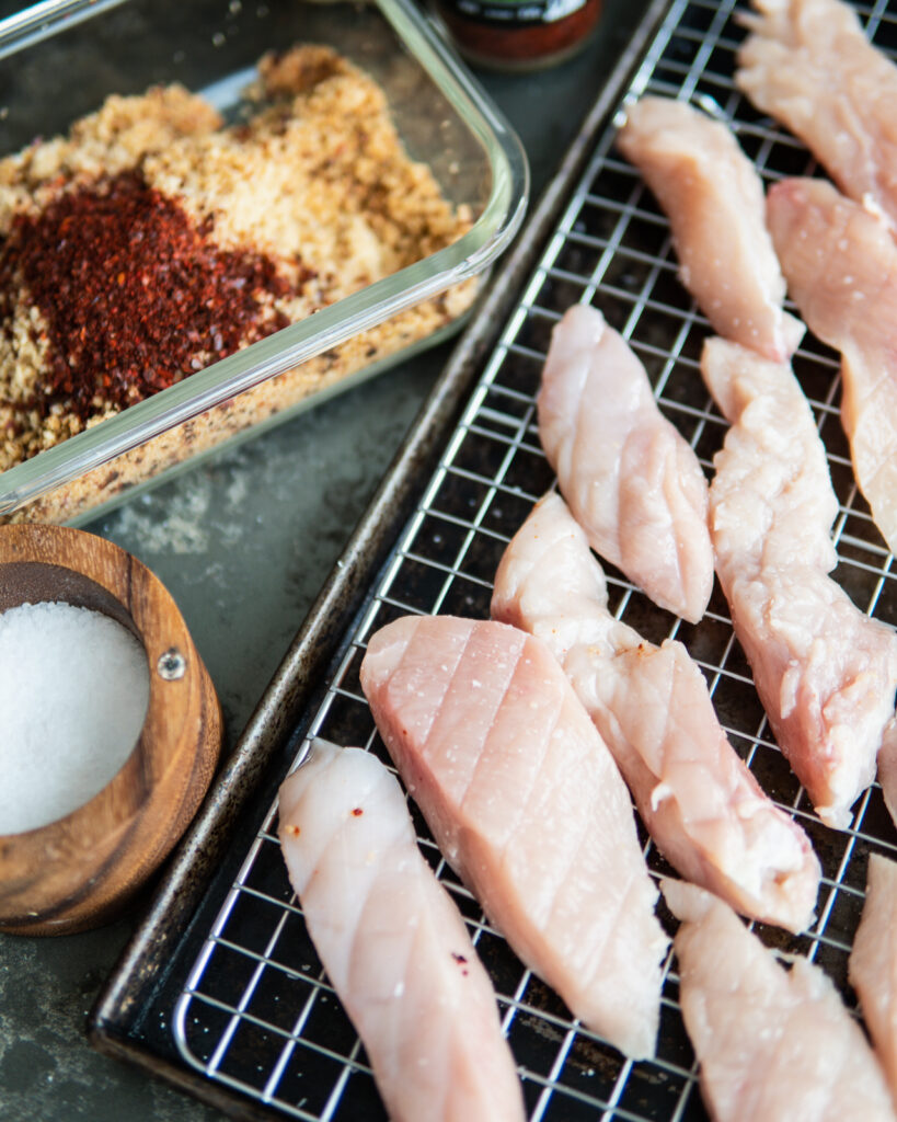 Raw sliced chicken breast into tenders on a baking sheet and rack.