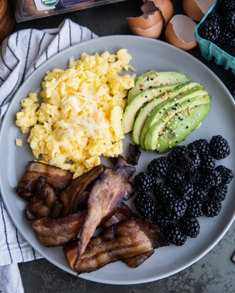 Cheesy egg scramble with crispy sheet pan bacon, avocado and blackberries on a plate.