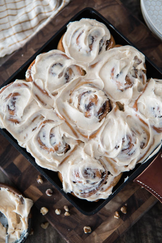 Frosted Black Walnut Cinnamon Rolls with Brown Butter Cream Cheese Frosting.