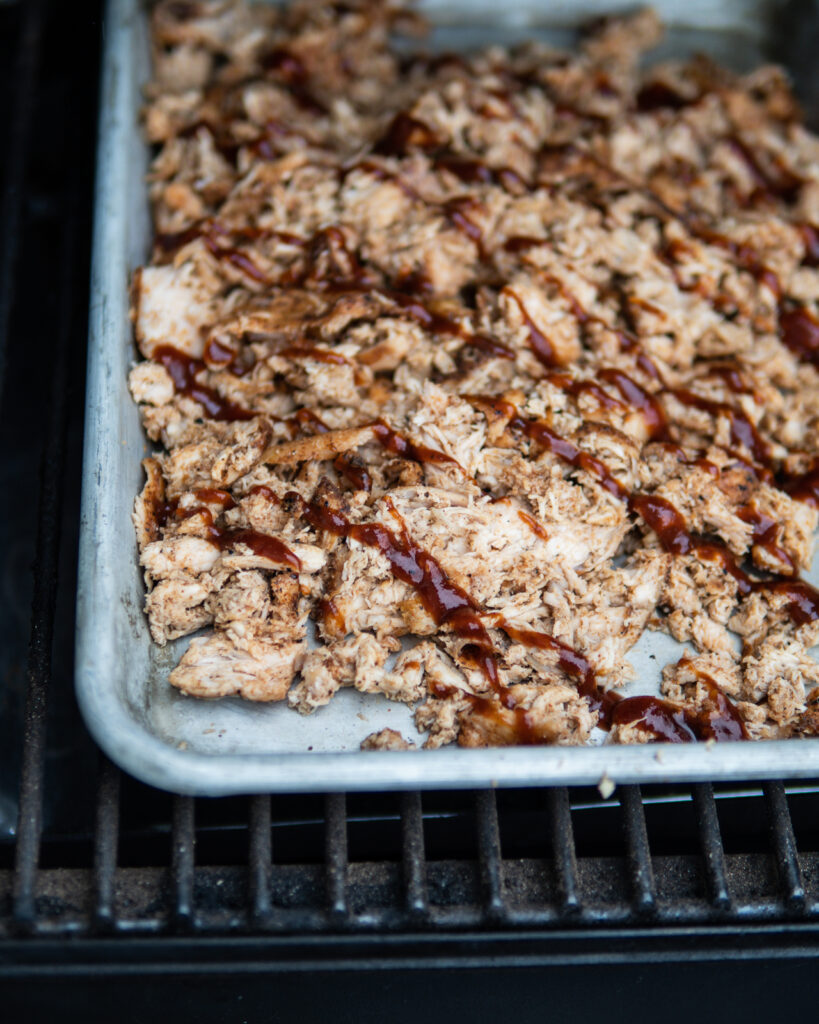 Sheet pan of shredded smoked chicken and bbq sauce.