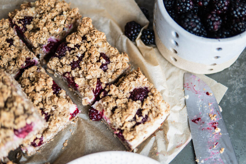 Sliced Blackberry Cheesecake Oat Bars on table surface with blackberries.