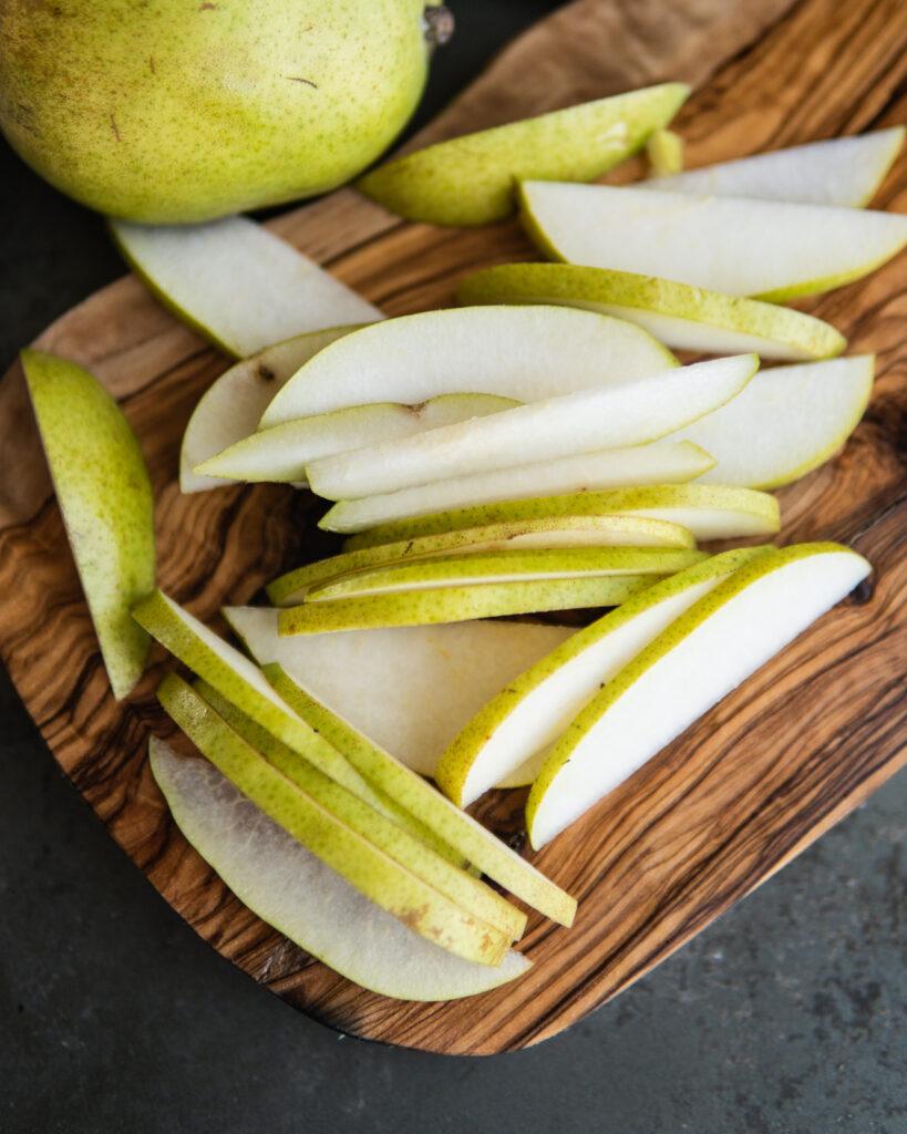 D'anjou pears sliced on a cutting board.