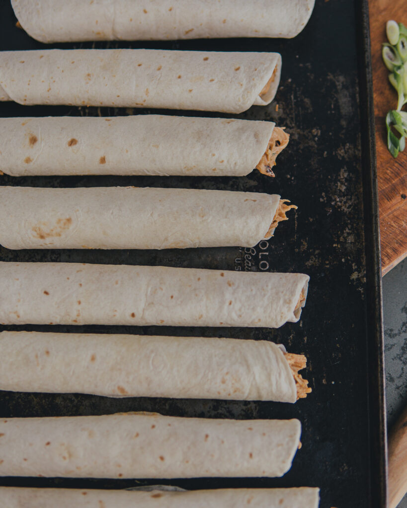 Chicken stuffed, rolled taquitos on a baking sheet.