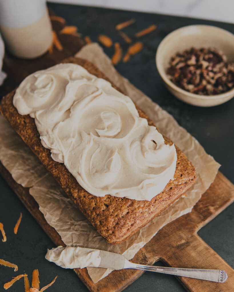 Finished Cardamom Carrot Loaf w/ Brown Butter Maple Cream Cheese Frosting swirled on top.