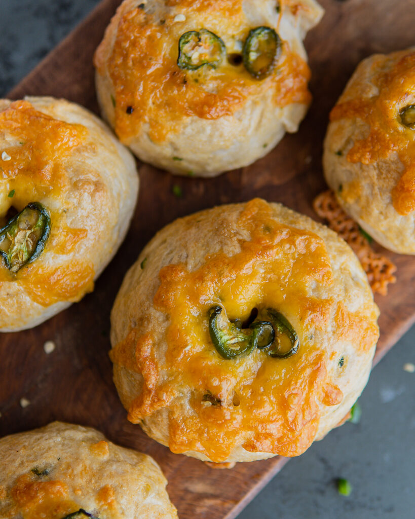 Baked and cooled Jalapeño Cheddar Bagels on a cutting board.