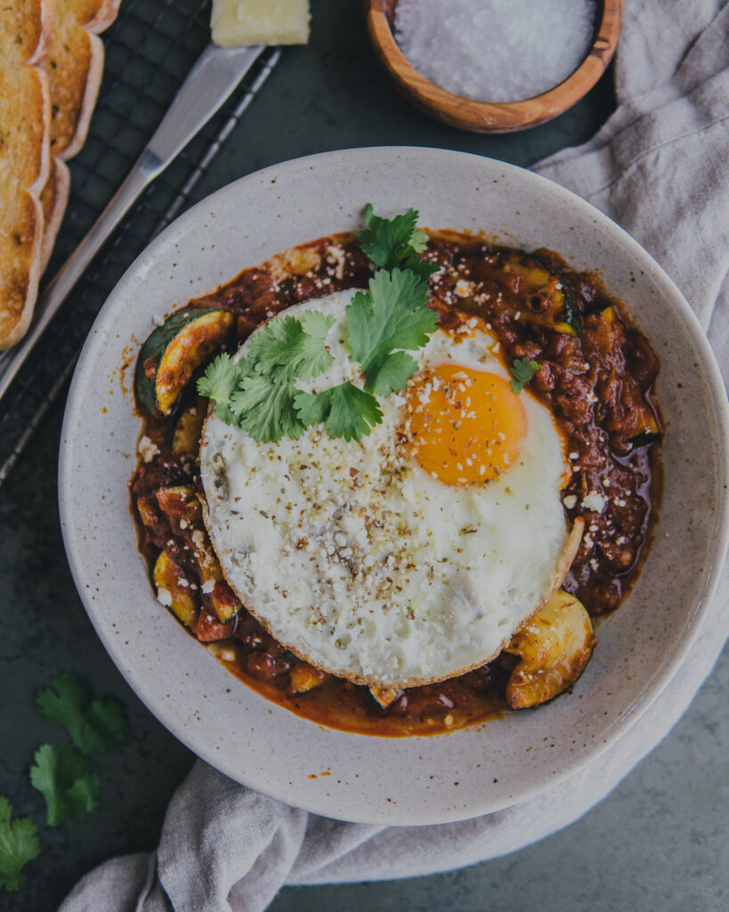 Full bowl of Sunday Brunch Shakshuka with a fried egg on top.
