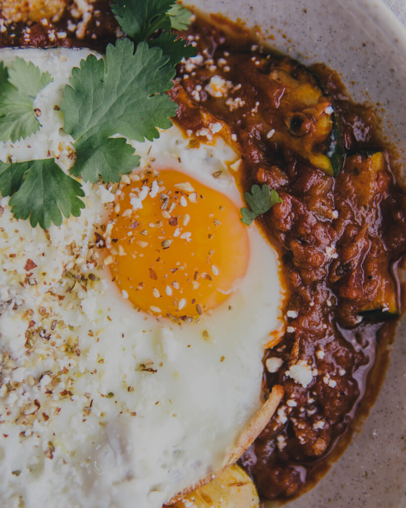 close up on bowl of Sunday Brunch Shakshuka with a fried egg on top.