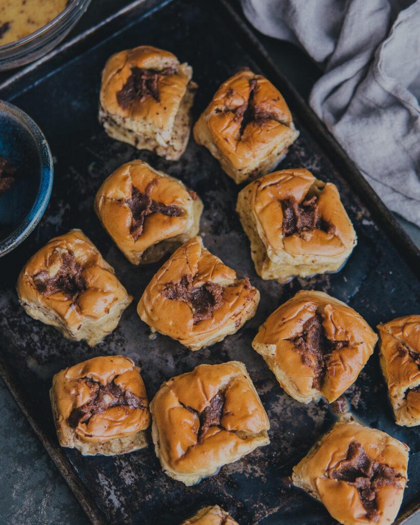 Prepped Hawaiian rolls on a baking sheet.