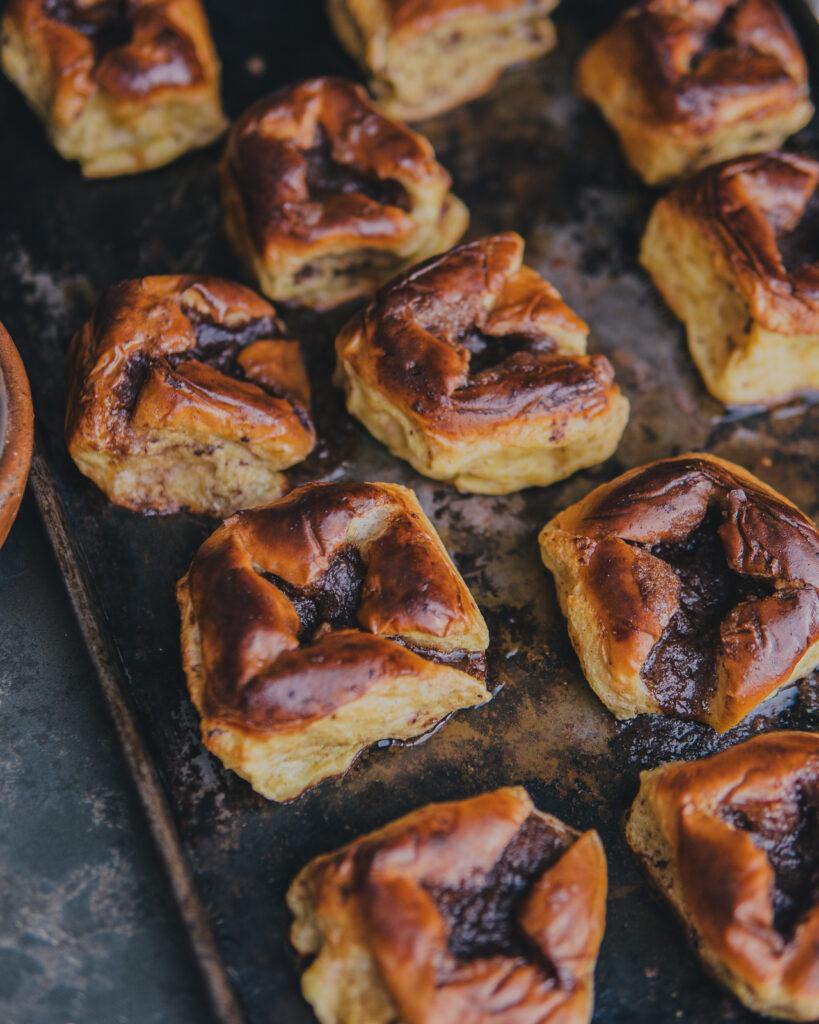 Baked Hawaiian rolls on a baking sheet.