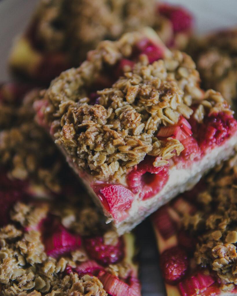 Close up of sliced Raspberry & Rhubarb Cheesecake Oat Bars.