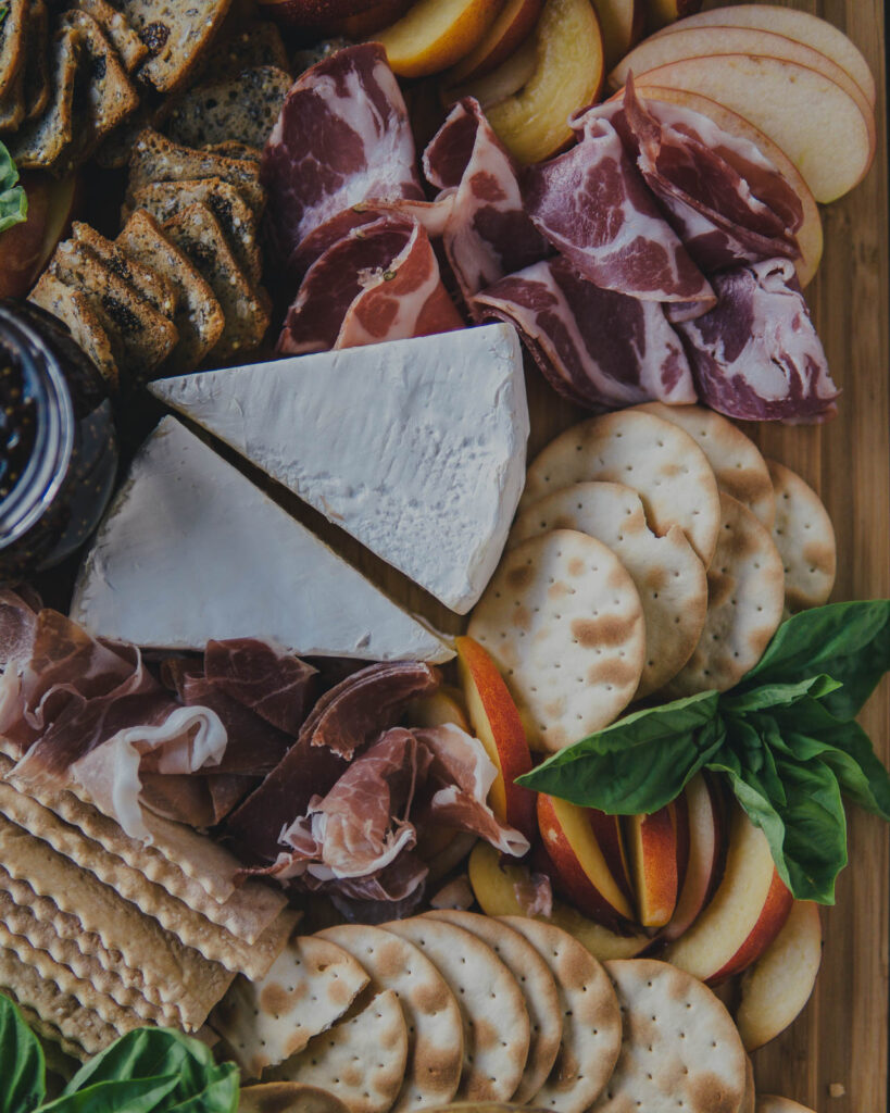 Close up on Summer Charcuterie Board Spread of meats, water crackers nectarine slices and brie.