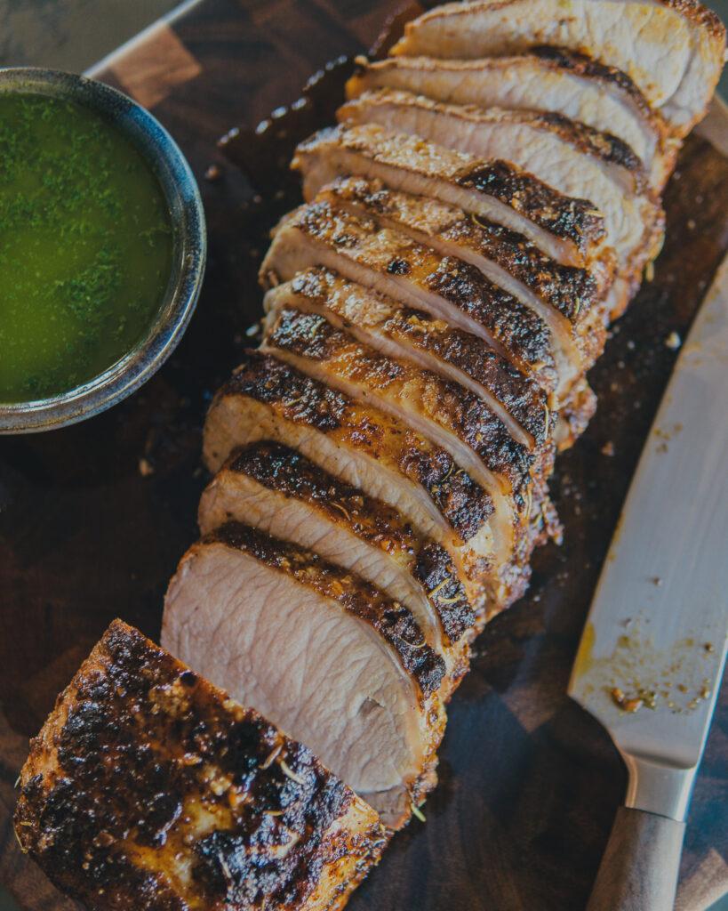 Sliced pork loin roast on a cutting board.