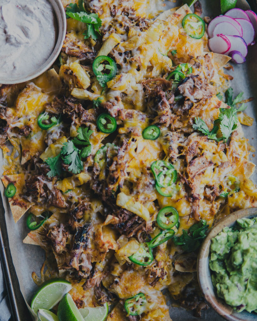 Full sheet pan of nachos with the sour cream dip top left and the grace pictures bottom right.