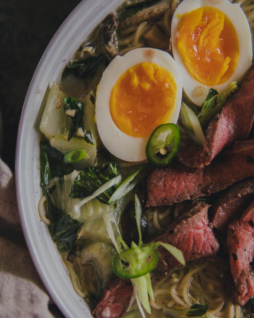 Close up on soft boiled eggs int eh Thai Green Chili Steak Ramen with Lemongrass Coconut Mushroom Broth.