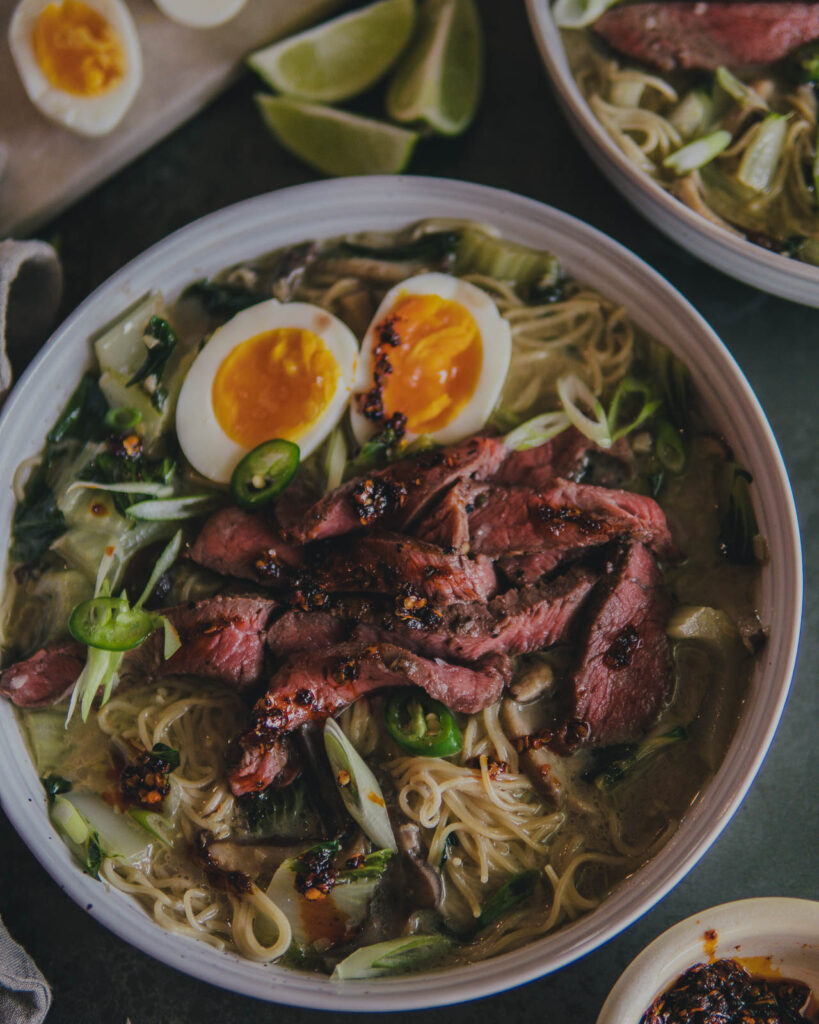 Finished bowl of Thai Green Chili Steak Ramen with Lemongrass Coconut Mushroom Broth with soft boiled eggs.