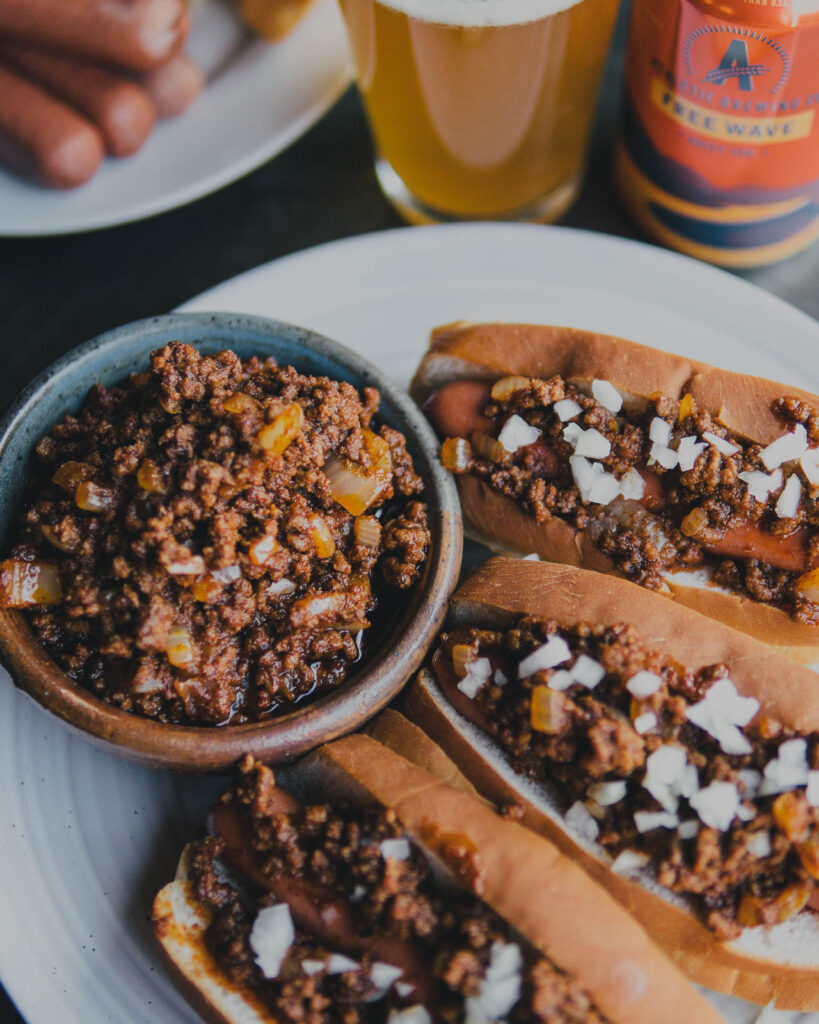 Athletic Brew Free Wave Chili Dogs on a plate with a bowl of chili on the side.