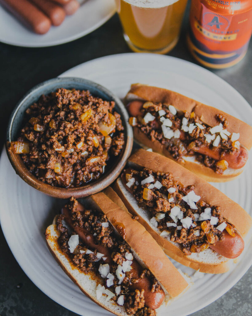 Three Athletic Brew Free Wave Chili Dogs on a plate with a bowl of Free Wave Chili on the side.