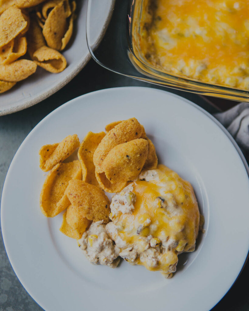 Cheesy Elote Dip with corn chip dippers on a plate.