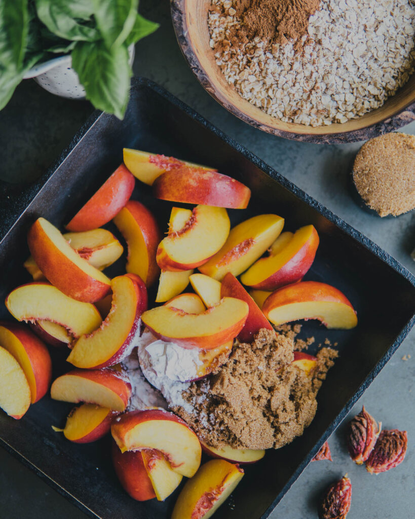 Sliced nectarines in cast iron skillet with brown sugar, cornstarch and oats.
