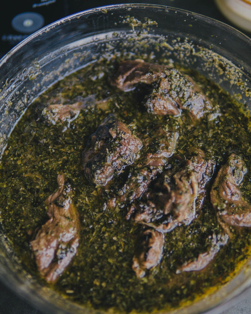 ButcherBox steak tips in a large glass bowl with the marinade.
