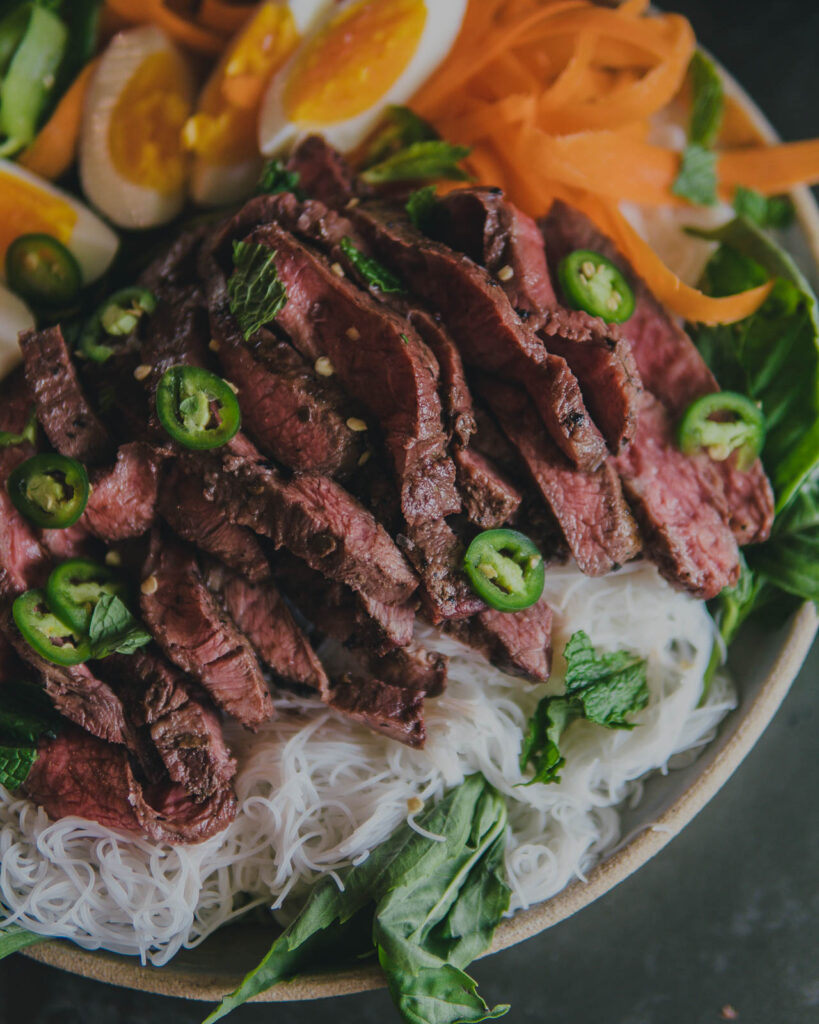 Rice noodle salad with steak, closeup of thai green chili steak.