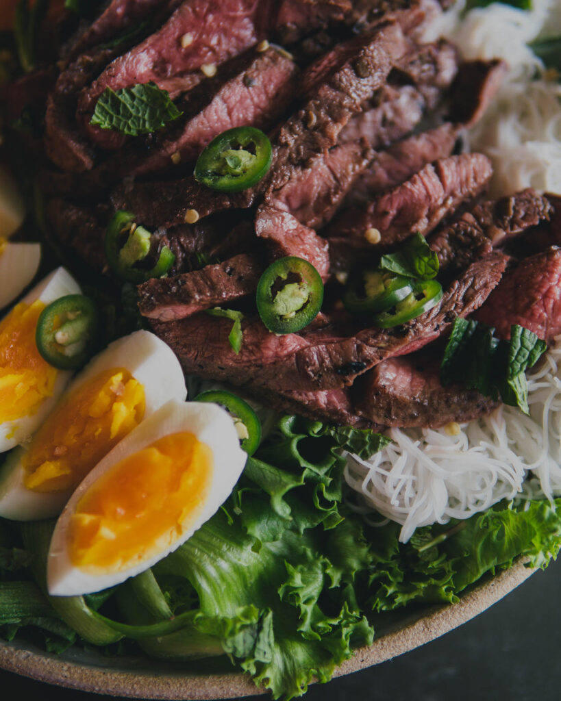 Bed of little gem lettuce and vermicelli noodles topped with Thai Green Chili steak, serrano pepeprs and soft boiled eggs.