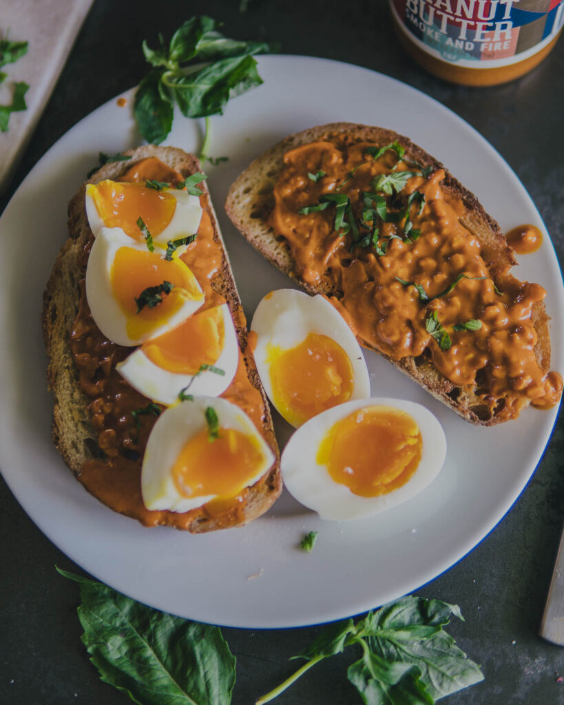 Smoke & Fire Peanut Butter Toast on a plate with soft boiled eggs and basil.