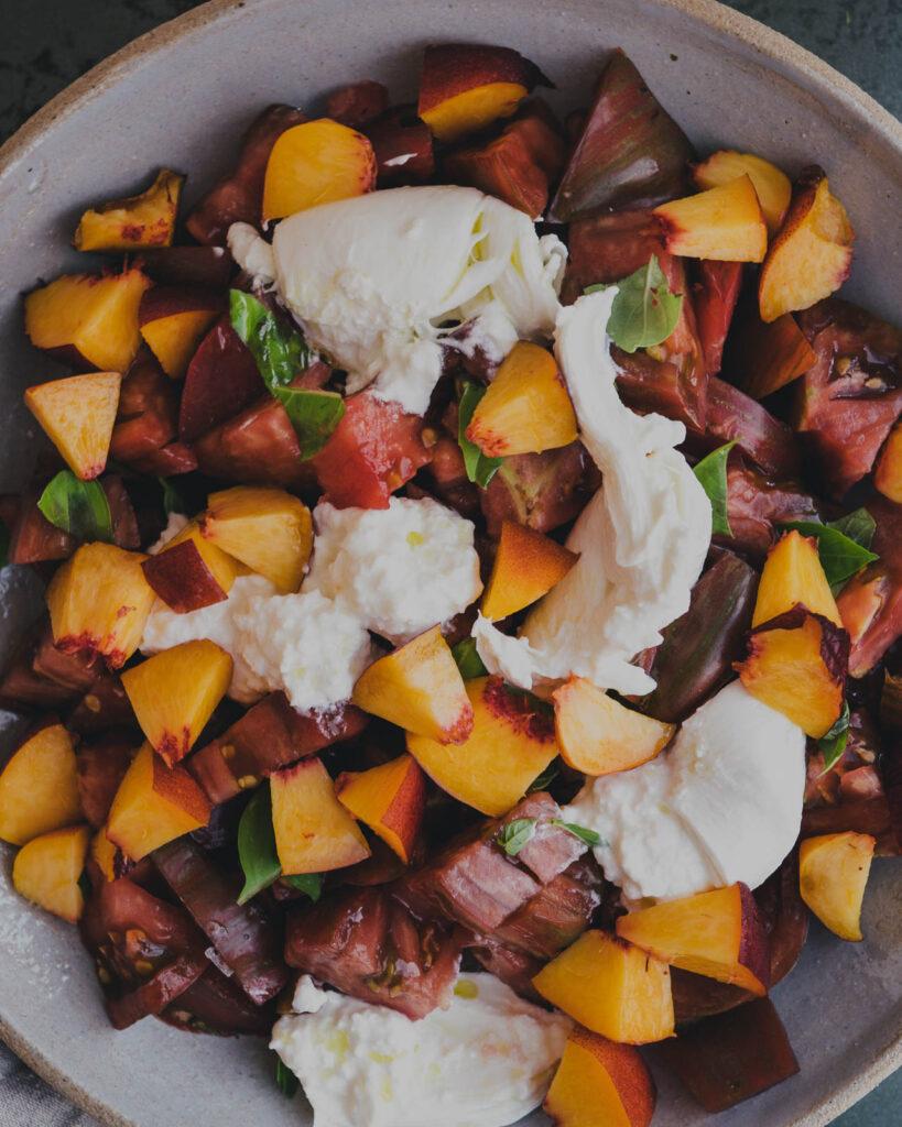 Closeup of heirloom tomato & peach burrata salad in a serving bowl.