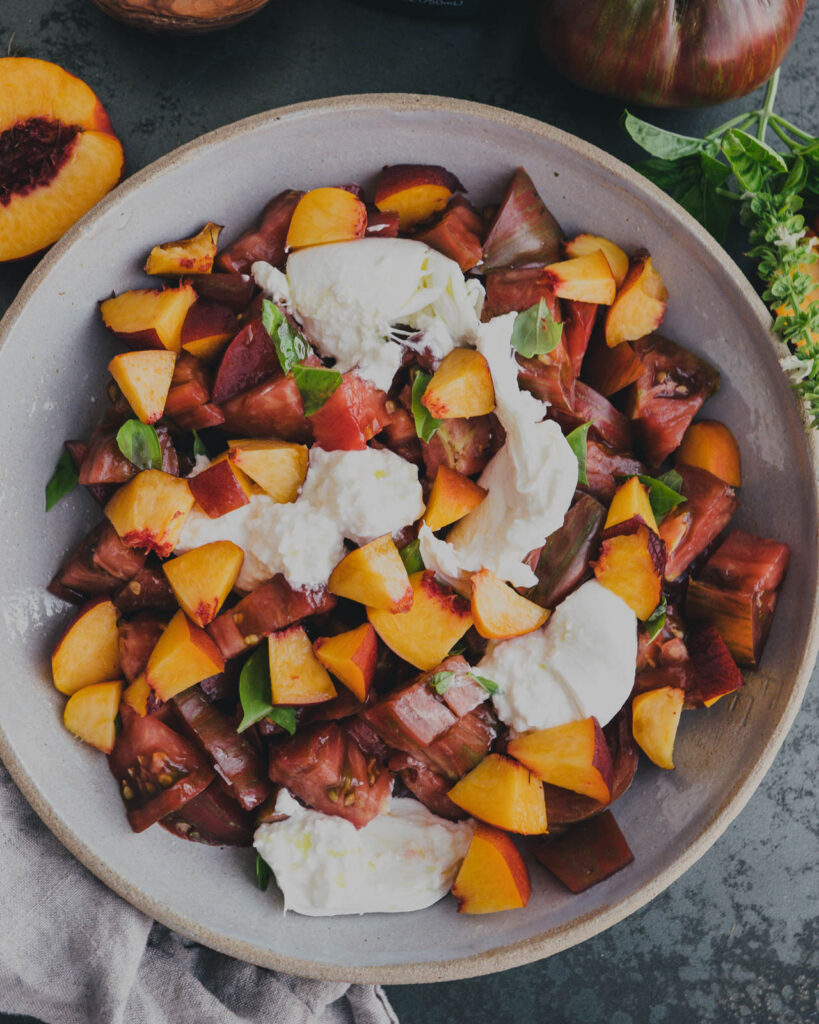 Heirloom tomato and peach burrata salad with basil and olive oil and flaky salt in a serving bowl.