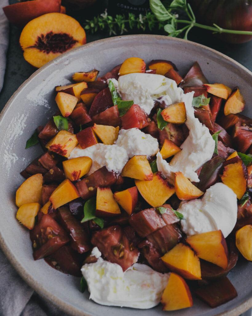 Heirloom tomato & peach burrata salad topped with fresh basil.
