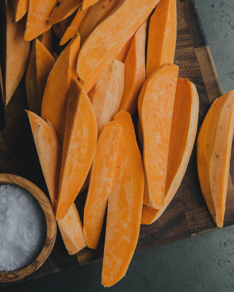 Peeled sweet potato wedges and flaky salt.