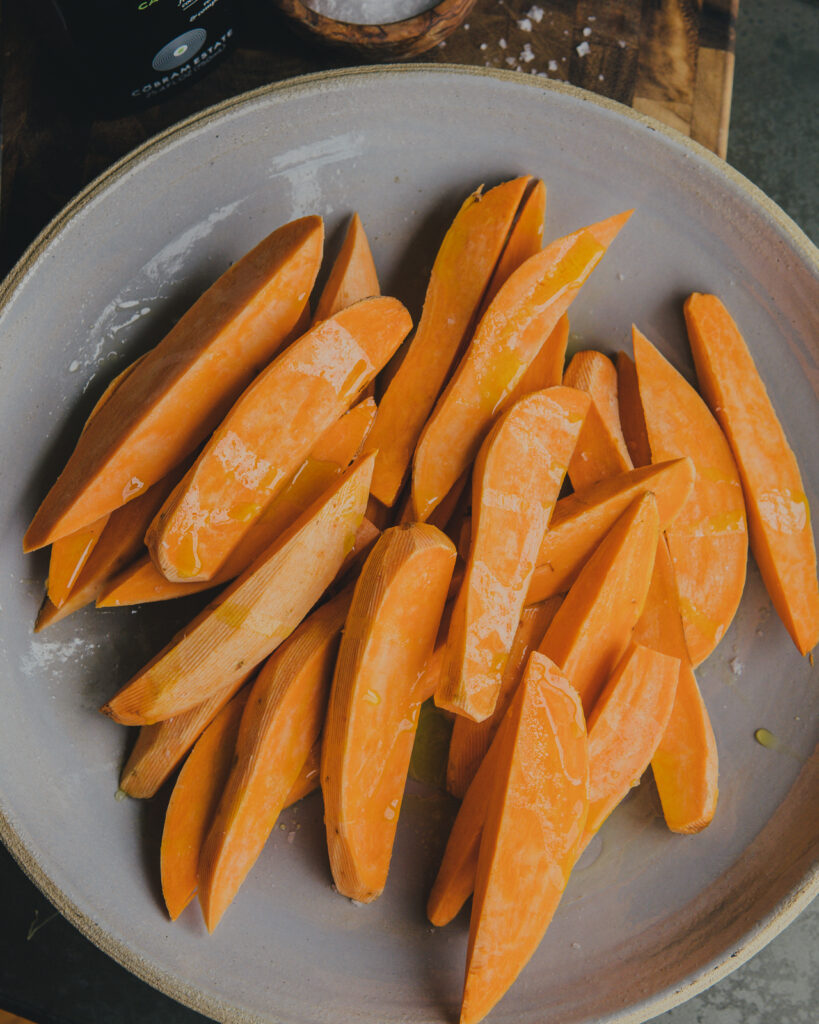 Peeled sweet potatoes cut into wedges.