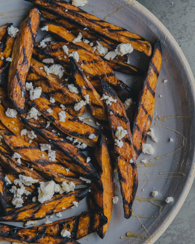 Grilled sweet potato fries topped with goat cheese and drizzled with hot honey.