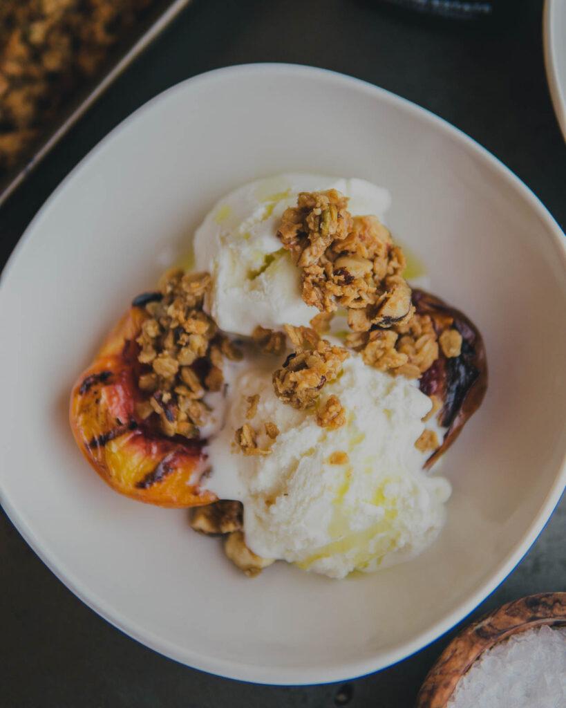 Grilled peach, granola, vanilla ice cream & EVOO in a bowl.