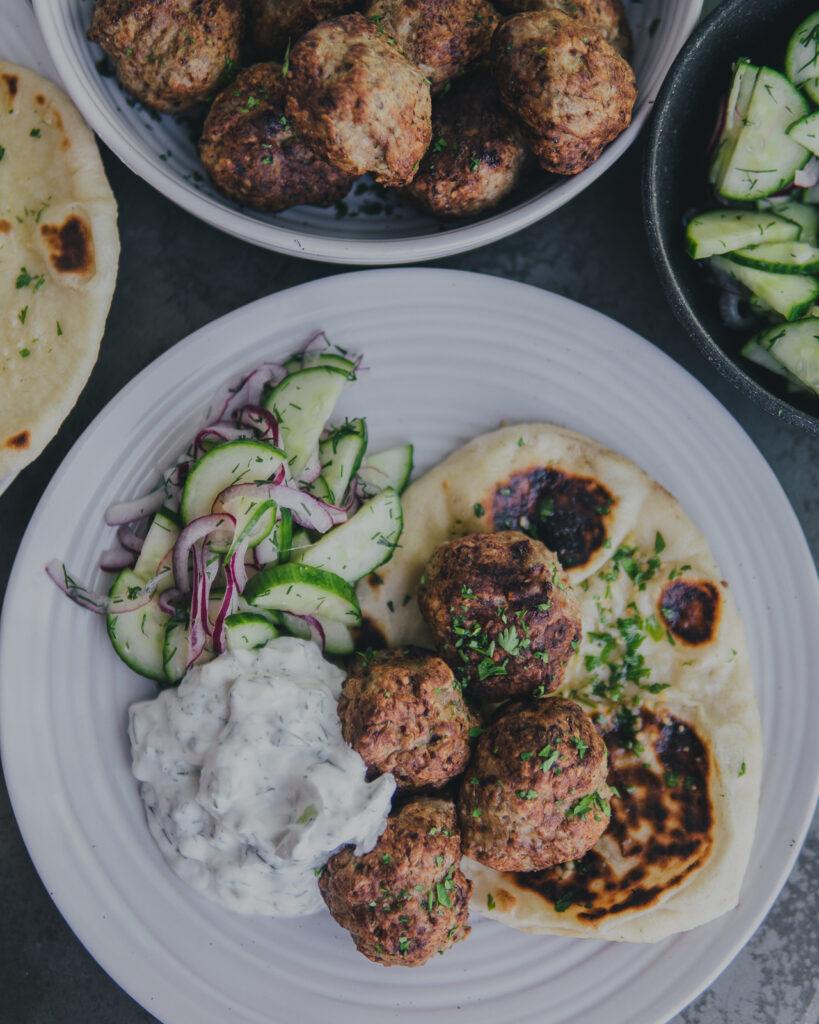 A finished plate of naan bread, AirCrisp Greek Meatballs w/ Cucumber Salad and tatziki sauce.